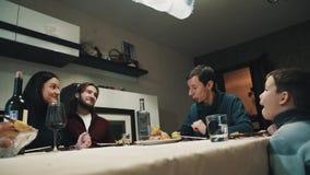 A família e o amigo na tabela de jantar têm bebidas e aderem-se vidros, celebração vídeos de arquivo