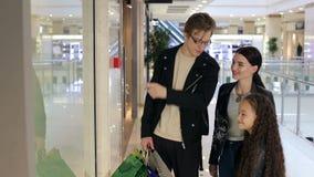 A família elegante com uma criança faz compras em um shopping moderno video estoque