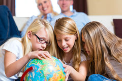 Família em casa, as crianças que jogam com um globo Fotografia de Stock Royalty Free