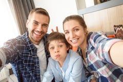 Família em casa que senta-se no sofá na sala de visitas que toma junto os pais das imagens do selfie que fazem chifres ao filho a imagem de stock royalty free