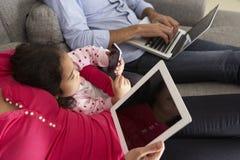 Família em Sofa With Smartphone, no portátil e na tabuleta de Digitas Foto de Stock Royalty Free