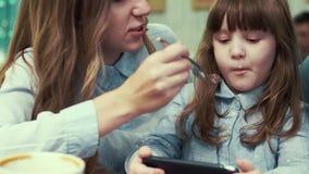 A família em um café, mamã alimenta sua filha, e os desenhos animados de observação da menina no telefone filme