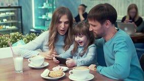A família em um café, paizinho, mamã, filha na tabela que olha algo no telefone e para discutir, sorri video estoque