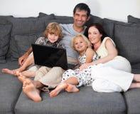 Família em um sofá com portátil Fotos de Stock Royalty Free