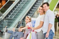 A família empurra crianças no carrinho de compras fotos de stock
