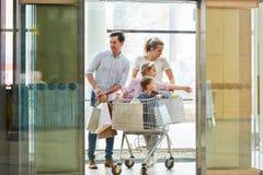 A família empurrar crianças na compra do quando do carrinho de compras imagem de stock