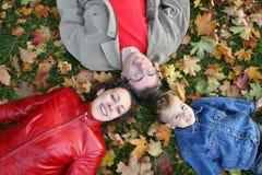 A família encontra-se nas folhas de plátano fotografia de stock royalty free