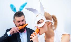 A família engraçada comemora a Páscoa Coelhos da Páscoa Bunny Couple Boas festas Os pares com orelhas do coelho estão comendo a c foto de stock royalty free