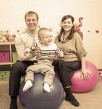 Família engraçada do moderno que salta em bolas da aptidão na sala de jogos Fotos de Stock Royalty Free