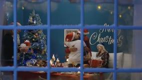 Família entusiasmado que troca com os presentes no Natal filme