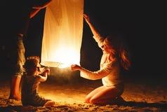 A família envia a ar a lâmpada celestial da lanterna elétrica em voo na praia imagens de stock royalty free