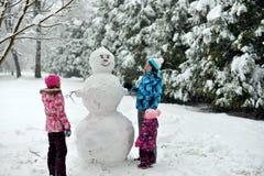 A família esculpe um boneco de neve grande na floresta no inverno fotografia de stock