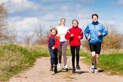 A família está correndo fora Fotografia de Stock Royalty Free