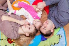 A família está encontrando-se no assoalho com seu bebê imagem de stock royalty free