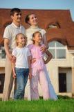 A família está na grama de encontro à casa imagem de stock