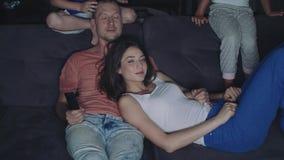 A família está olhando a tevê na noite vídeos de arquivo