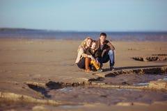 A família está sentando-se na areia e no sorriso Imagem de Stock