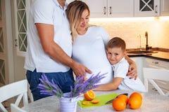 A família está tendo o café da manhã e está cortando laranjas na tabela fotos de stock royalty free