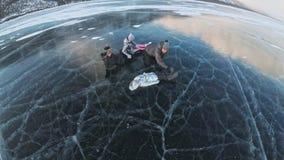 A família está tendo o divertimento no gelo bonito nas quebras A luta engraçada do filho e da filha da mãe do pai no gelo, faz o  filme