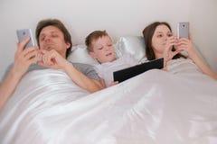 A família está usando os telefones e a tabuleta dos dispositivos móveis que encontram-se na cama na manhã imagem de stock