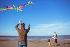 A família está voando um papagaio no litoral Imagens de Stock