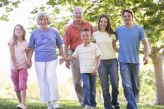 Família extensa que anda nas mãos da terra arrendada do parque Imagem de Stock