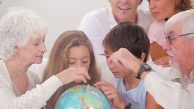 Família extensa que olha o globo Foto de Stock