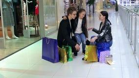 Família feliz alegre que olha sua compra na loja, abraçam na alameda filme