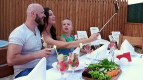 A família feliz, almoço, pais com crianças faz as fotos no telefone celular é colocada em um selfi da vara, alegre video estoque