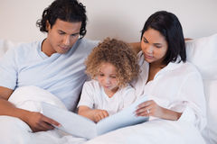 A família feliz aprecia ler um livro junto Fotografia de Stock