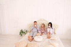 A família feliz bebe o chá ou o café nos pijamas que sorri e que olha fotos de stock royalty free