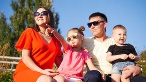Família feliz bonita Sentam-se em um banco de parque, óculos de sol Filha pequena que aponta seu dedo no céu imagem de stock