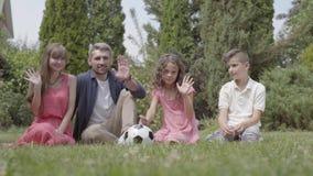 Família feliz bonito do retrato que senta-se na grama no jardim junto Mãe, pai, filho, e filha que olha no video estoque