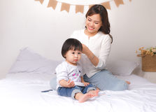 Família feliz, cabelo de escovadela da mãe nova bonita de seu adorab fotografia de stock