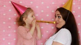 A família feliz - chifres de sopro do partido da mãe e da filha, sorrisos, abraços, riso e comemora o aniversário Uma mulher e el video estoque