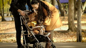 Família feliz com as crianças que andam no parque do outono vídeos de arquivo