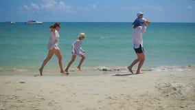 Família feliz com as crianças que andam no Sandy Beach Ilha tropical, em um dia quente video estoque