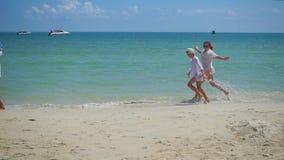 Família feliz com as crianças que andam no Sandy Beach Ilha tropical, em um dia quente filme
