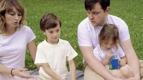 Família feliz com as crianças que descansam na grama durante um piquenique Felicidade e harmonia na vida familiar video estoque