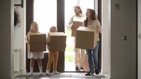 Família feliz com as crianças que guardam a casa entrando da porta de abertura das caixas video estoque