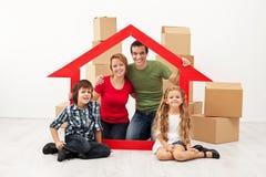 Família feliz com as crianças que movem-se em uma casa nova