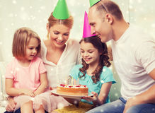 Família feliz com as duas crianças em chapéus do partido em casa Imagens de Stock Royalty Free