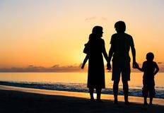 Família feliz com as duas crianças na praia do por do sol Foto de Stock