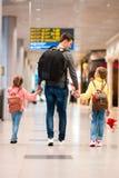 A família feliz com as duas crianças no aeroporto tem o embarque de espera do divertimento fotos de stock royalty free