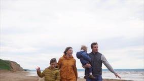 Família feliz com as duas crianças que andam na praia video estoque