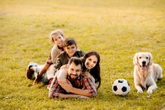 Família feliz com as duas crianças que encontram-se em uma pilha na grama com assento do cão imagem de stock