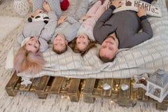 Família feliz com as duas crianças que encontram-se na cama Fotos de Stock Royalty Free