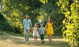 Família feliz com as duas crianças que guardam as mãos durante a caminhada recreacional no parque imagem de stock