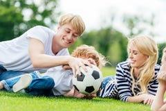 família feliz com as duas crianças que têm o divertimento com bola de futebol ao encontrar-se fotos de stock