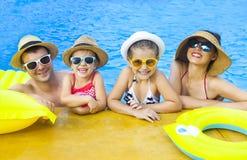 Família feliz com as duas crianças que têm o divertimento na piscina Fotografia de Stock Royalty Free